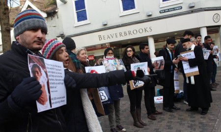 Several people gather in the street holding placards